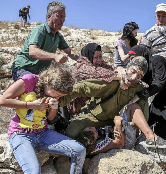 Ahed in her younger years. Here seen biting the hand of an Israeli soldiers who refused to respond to being beaten up by the entire Tamimi family.