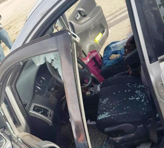 "This car which was hit near Kiryat Arba had both front windows smashed. If you look carefully, you can see the ""rock"" in the passenger seat."