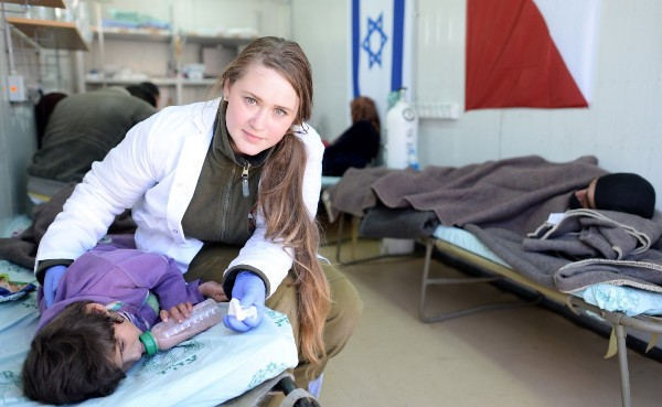 An Israeli doctor in a makeshift clinic on the Israel Golan Heights treating a Syrian child. Also note the adult on the cot on the right (photo: Israel21C).