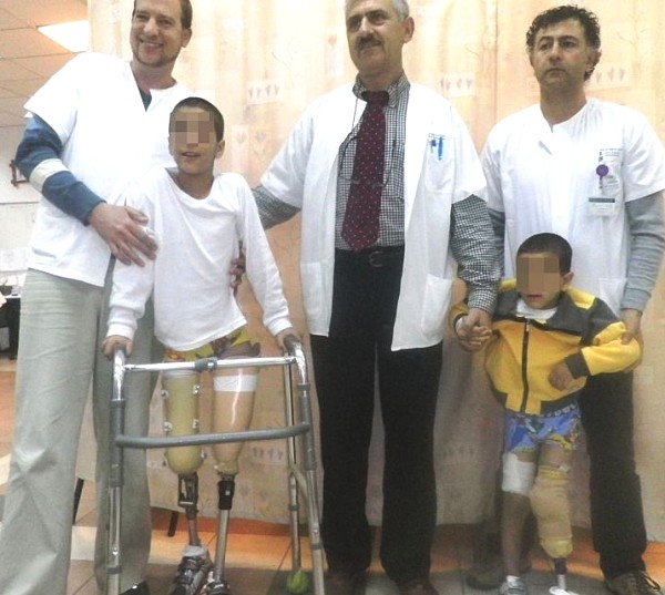 Two Syrian children who were provided prosthetic legs at the Zif Hospital in Tzfat. The boys are with their fathers--with the Israeli doctor in the middle.