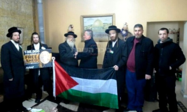Note the Palestinian flag that the Neturei Karta are holding and the picture in the background.