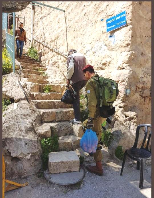 This picture of an Israeli soldier helping an elderly Palestinian man carry his groceries up steep steps in Hevron speaks volumes.