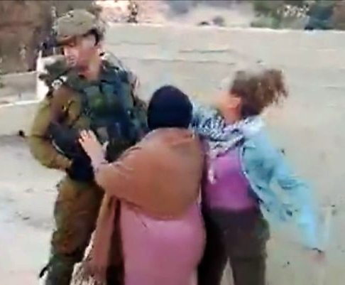 This is blurry photo shows part of the incident in which Ahed Tamimi (right) and her mother (center), slapped and kicked an IDF soldier. Note that the soldier did not respond.
