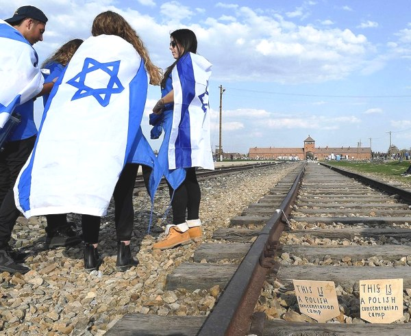 """A photo taken at the March of the Living yesterday--this one obviously from Birkenau. Note the cardboard """"This is a Polish Concentration Camp"""" signs put on the tracks."""