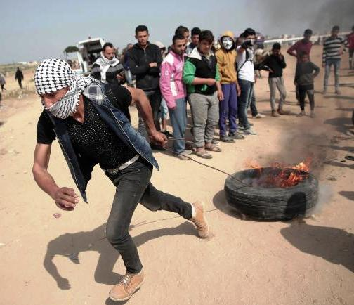 """A Palestinian man drags a burning tire during a protest at Gaza's border with Israel on Friday."""